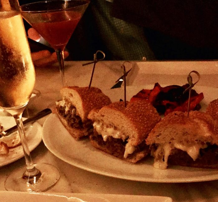 Pieces of cheesesteak served on a fancy next to champagne and rose petals