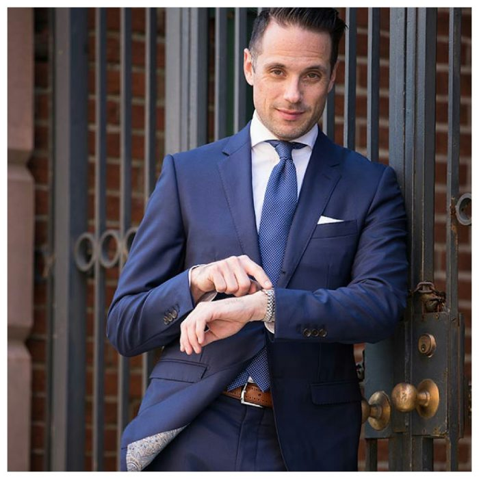 Man with blue suit Man standing with two-piece suit. of two pieces, pointing his watch with his finger