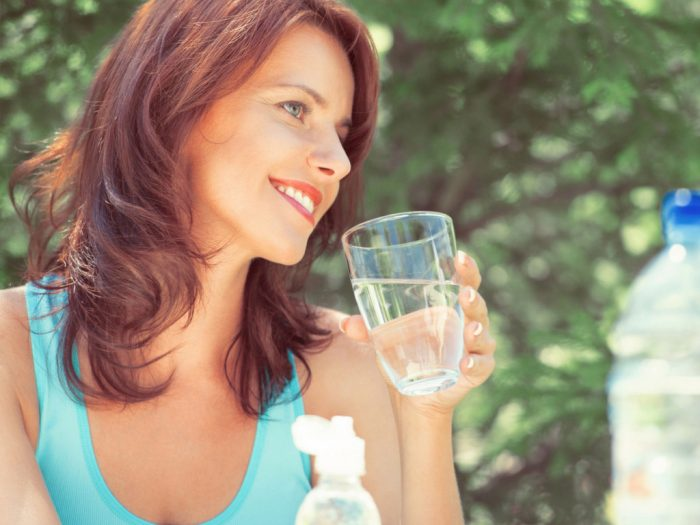 Woman with long hair and smiling holding a glass of water
