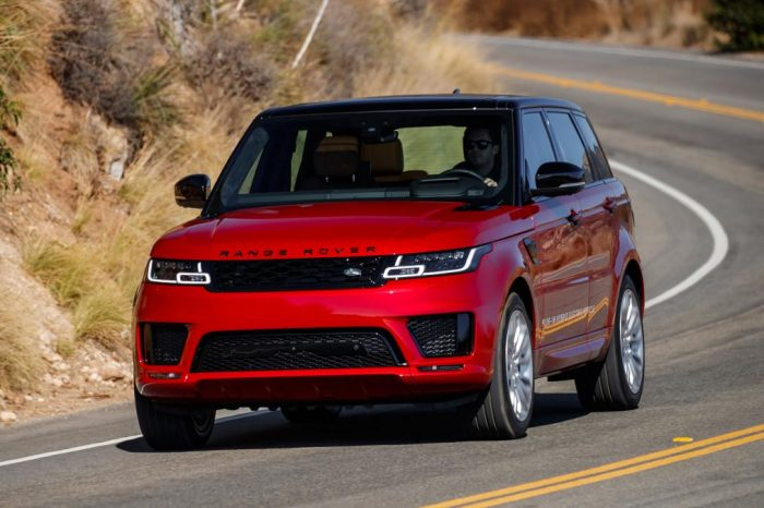 Vehicle Range Rover Sport red color with black roof. Presents external accessories in black. It goes down a road where you can see a previous curve and the white and yellow lines framing it. Around the left we see mountainous vegetation somewhat arid