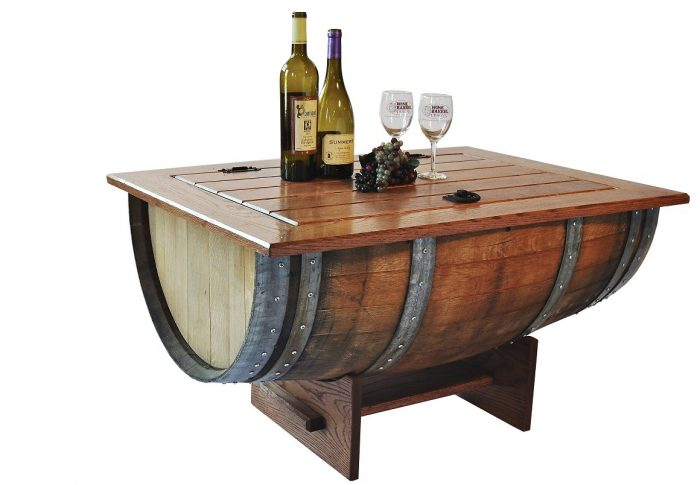 Wooden table made with half a barrel. It has a mahogany support base with two vertical boards joined by a table located horizontally of the same elongated color which unites them. On each side of the stand a long handle comes out. The upper part of the table is designed as a table in the form of a door formed by five long boards joined together, with an iron handle to open and two hinges. Above the table you can see two bottles of wine of different size and shape, a bunch of grapes and two glasses of glass