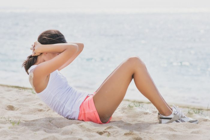 A young woman doing exercises with sports clothes on the sands of a beach
