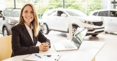 Lady sittin inside a dealership near a laptop