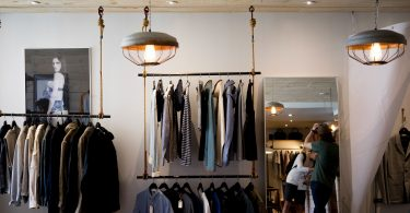 clothing store with racks of differents clothes a mirror and two man lamps on the ceiling