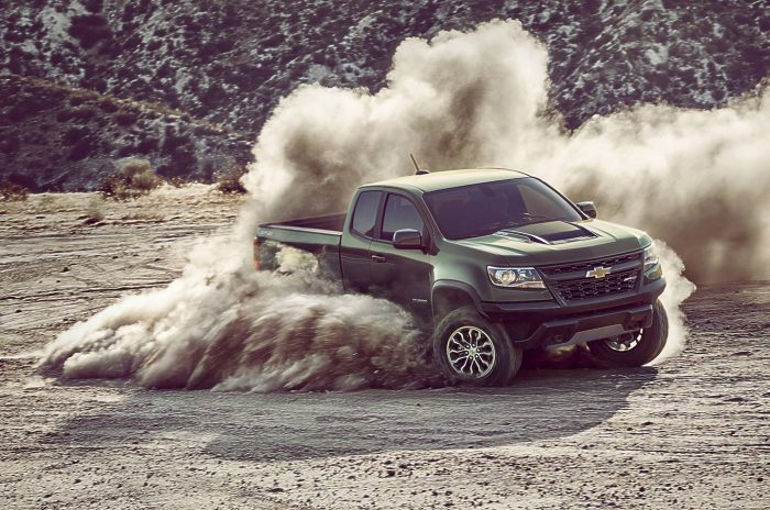 Chevrolet Colorado ZR2 truck of the year 2017. Olive green color. Sliding on terrain at high speed raising a lot of dirt and dust