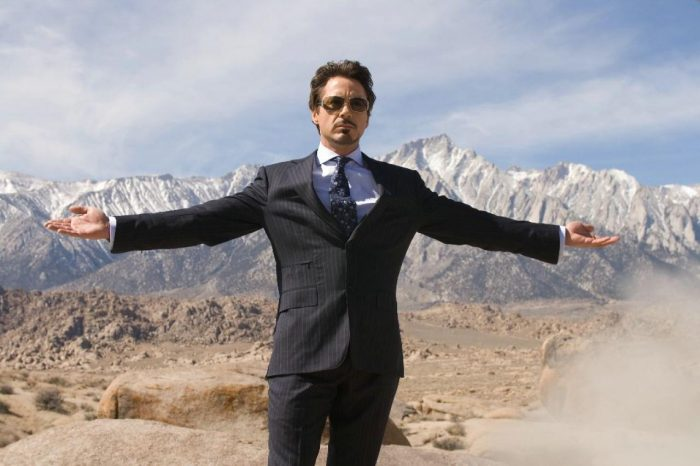 Man with blue suit on mountain with snow. Wear glasses and have arms extended sideways