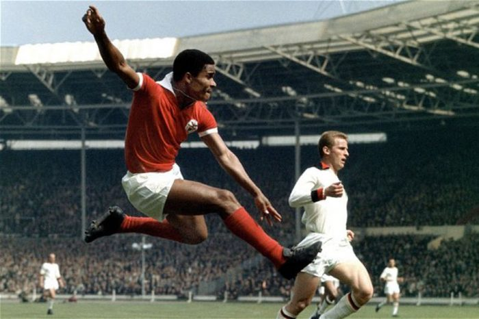 Player Eusebio jumping high inside the soccer field. Red flannel and white cut trousers. Extended arms