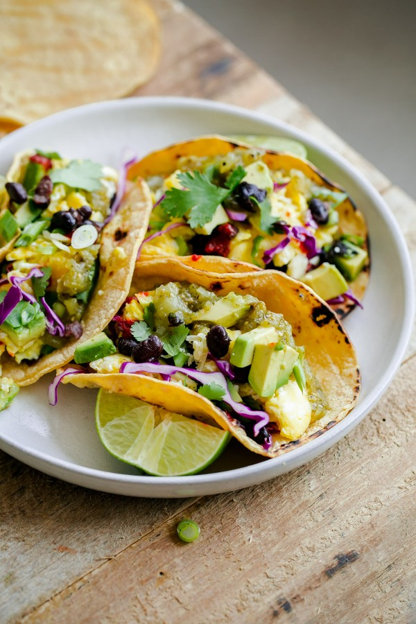 In a white bowl several tacos filled with asparagus and several vegetables are shown. Next to lemon slices