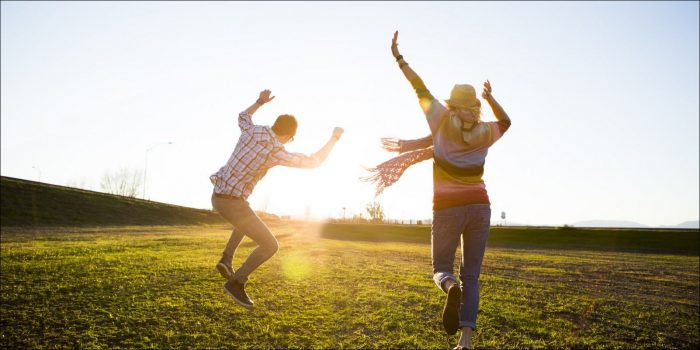 Couple running and jumping through a field towards a sunset. Both wear casual clothes. The woman is holding her arms up and the man is jumping with both arms up. Both from behind.