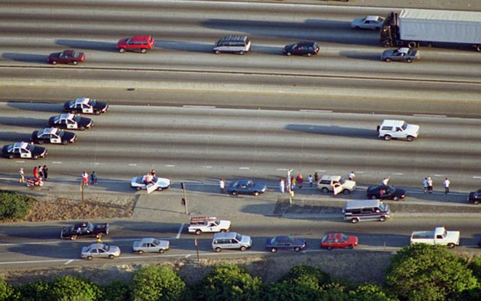 Motorway seen from afar with two circulation channels. There are parked vehicles and others in movement. Special focus on a white truck in full pursuit leading to O.J. Simpson.