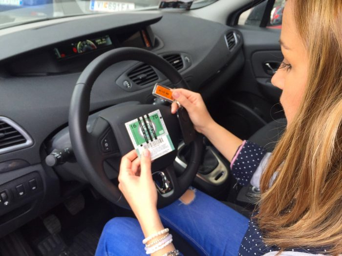 Long-haired woman sitting behind the wheel of a car looking at some tickets