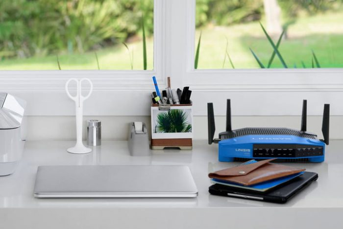 Router blue color located on a desk with white tonality with some objects around like folders, scissors, computer, teype tape, calendar. In the background a garden that can be seen through a window