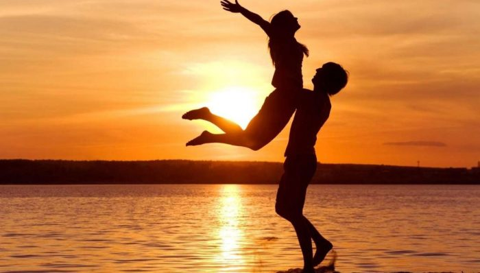Silhouette of couple on the shore of a beach with a beautiful sunset sun. He is carrying her around the waist and she is with outstretched arms