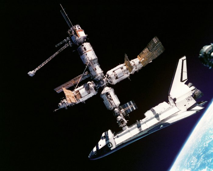 Space Station and Ferry located in space with their structures without apparent movement one geared to the other. Background part of the moon