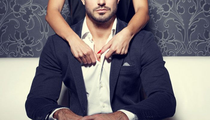 Man sitting at couch with woman behind and her arms wrapped around his shoulders
