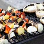 a grill with some veggies kabobs and slices of mushrooms