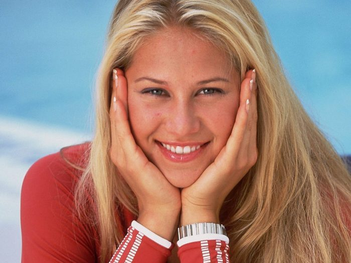 The international tennis player Anna Kournikova is seen posing with a flannel of lycra red sleeve, with her loose blond hair. She is smiling and with both hands gripping her face.
