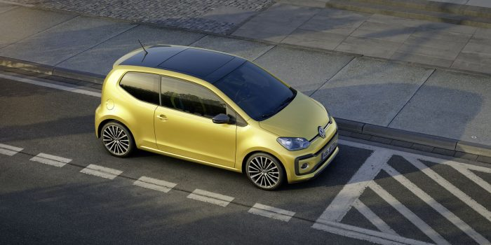 Volkswagen e Up parked on street with white signage, is ocher with black roof, two doors, star wheels in black and silver. Rear antenna in the middle