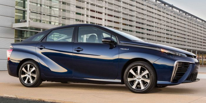 Toyota Mirai blue car parked next to gray buildings. Four doors and silver wheels, very bright