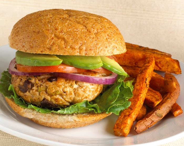 Hamburger with plenty of avocado and lemon juice, tomatoes and other vegetables. French fries around