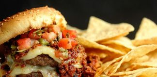 Hamburger with meat and cheese and in the side of the dish there are french fries