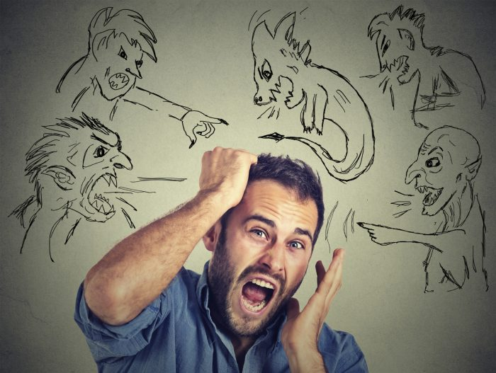 Evil men pointing at stressed anxious guy. Portrait desperate young businessman frustrated screaming isolated on grey wall background. Negative human emotions face expression feelings life perception