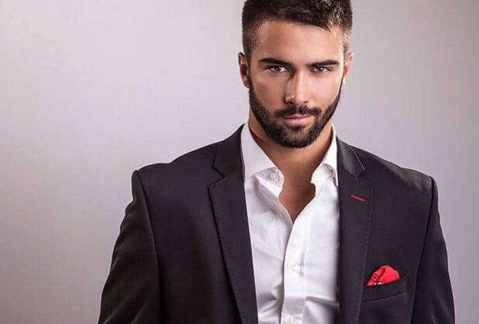 Man of fair complexion brunette with beard and dark suit without tie, white shirt.