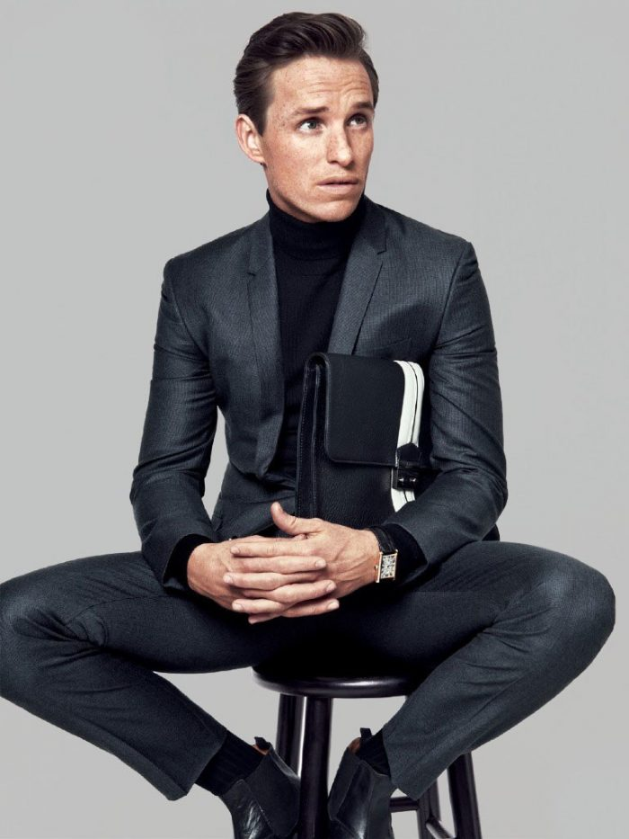 Sitting on a stool a man dressed in black leather suit. He has a briefcase under one of his arms