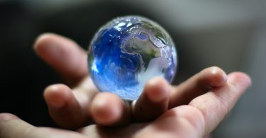 Marble that looks like world in someones hand