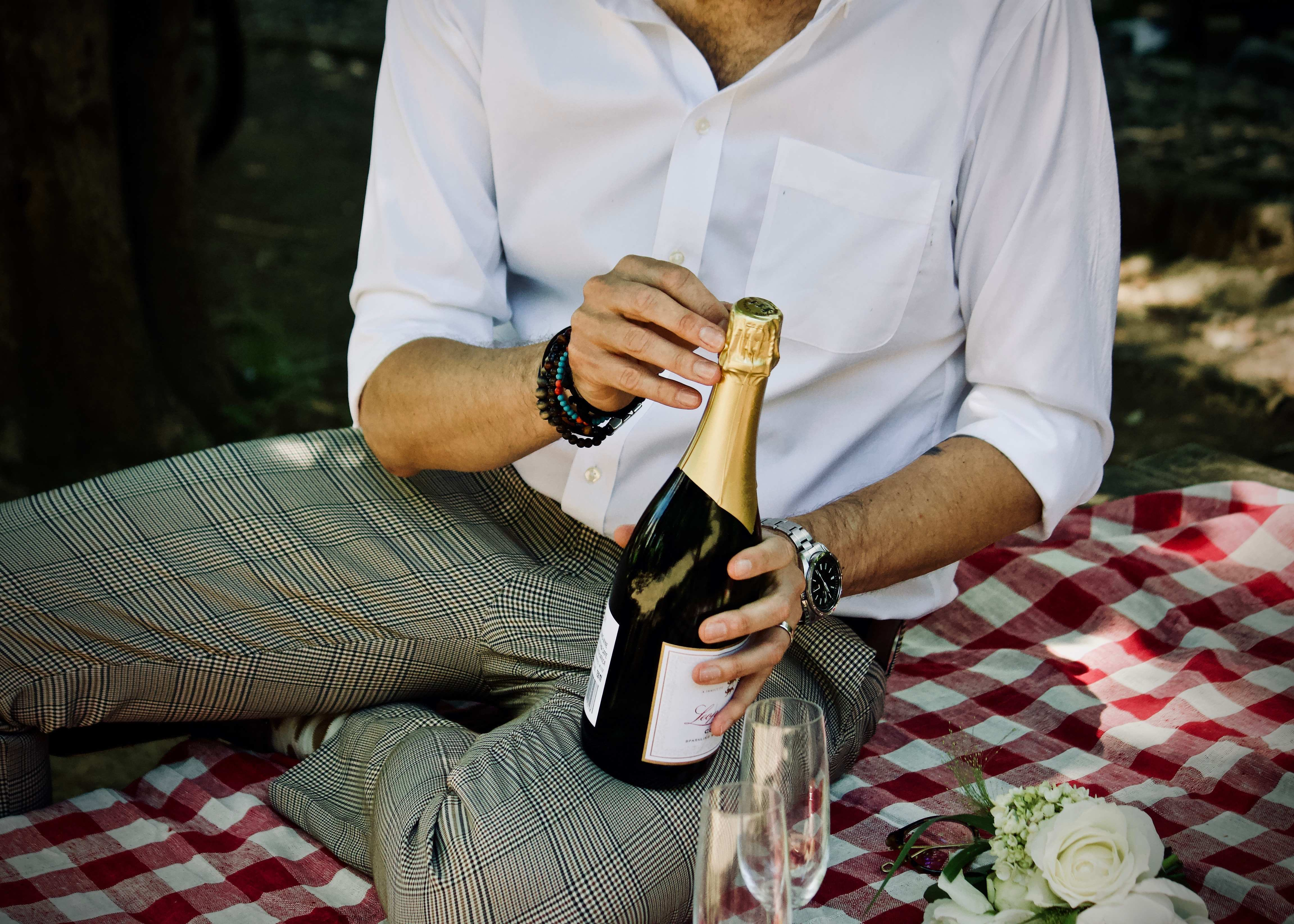 man opening champagne picnic date relationship