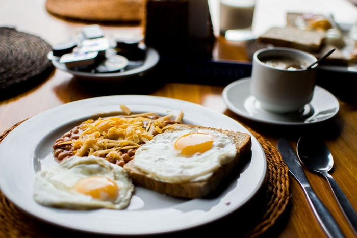 Breakfast plate with eggs, toast, beans, and a cup of coffee